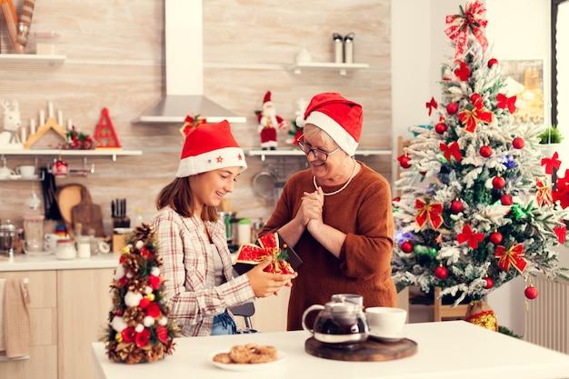 Oma schaut fröhliche nichte an, die weihnachtsgeschenke mit rotem hut genießt