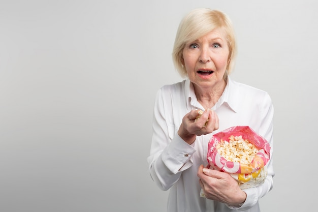 Oma sieht gerne cartoons, filme und verschiedene fernsehserien - so wie es junge leute so gerne tun. diese frau sieht aus wie eine sehr moderne alte frau.