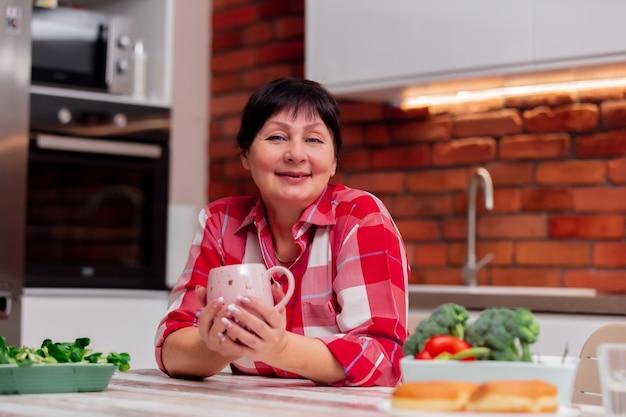 Oma sitzt am tisch in der küche, trinkt kaffee und ruht sich aus