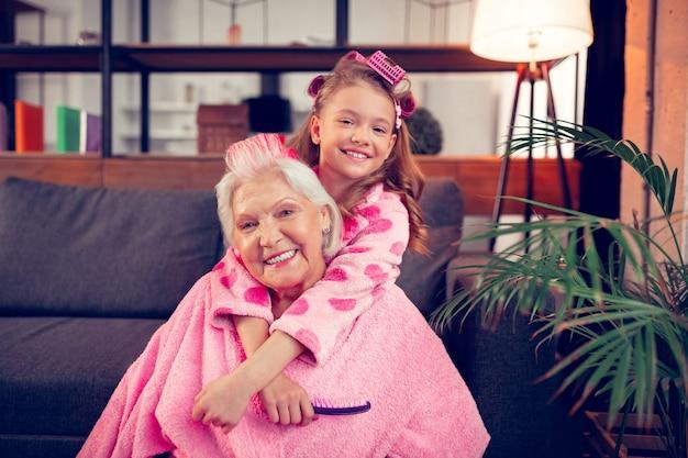 Oma umarmen. glückliche enkelin, die ihre oma umarmt, nachdem sie am wochenende lockenwickler zusammengebaut hat