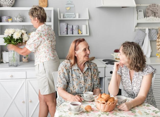 Oma und enkelin, die miteinander beim frühstücken sprechen