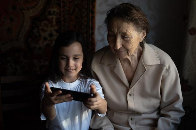 Oma und enkelin. ein süßes kleines mädchen zeigt ihrer großmutter ein smartphone.