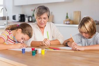 Oma und ihre Enkelkinder zeichnen ernst