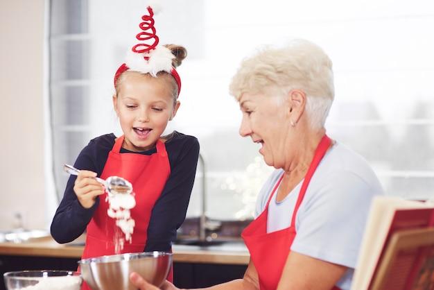 Oma und mädchen machen zusammen kekse