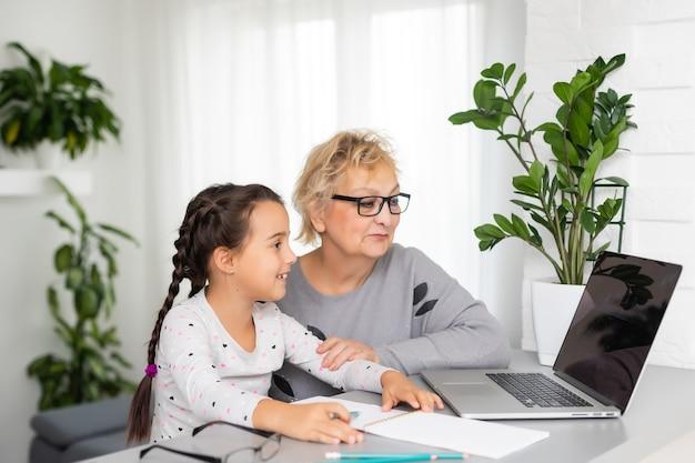 Oma und mädchen mit einem laptop