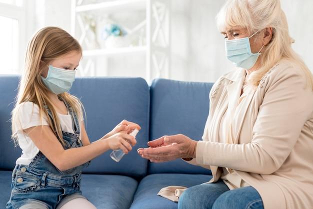Oma und mädchen mit maske mit desinfektionsmittel