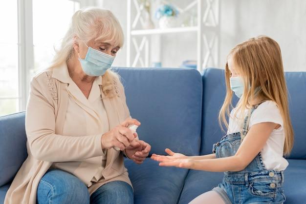 Oma und mädchen mit maske mit händedesinfektionsmittel