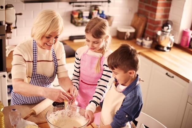 Oma und zwei kinder backen leckeren kuchen