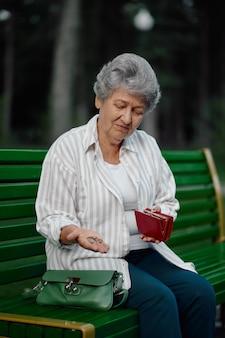 Oma zeigt im sommerpark eine kleinigkeit in ihrer brieftasche