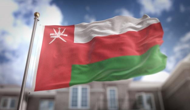 Oman-flagge 3d-rendering auf blauem himmel gebäude hintergrund