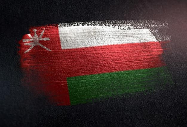Oman-flagge gemacht von der metallischen bürsten-farbe auf dunkler wand des schmutzes