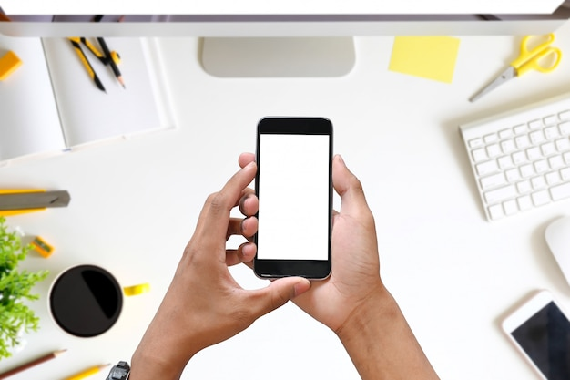 Oman-hände, die intelligentes telefon mit leerem kopienraumschirm auf schreibtisch halten.