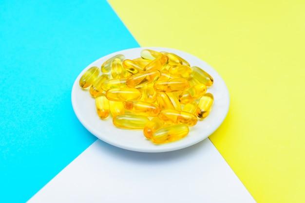 Omega 3 fischöl gel casules auf weißem teller auf weißem, blauem und gelbem hintergrund. kreatives gesundheitskonzept