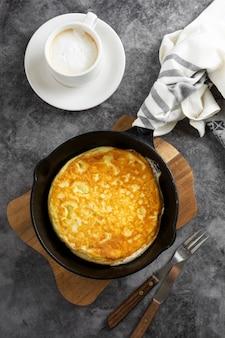 Omelett in der pfanne und tasse kaffee. frisch gekochtes gesundes omelett.