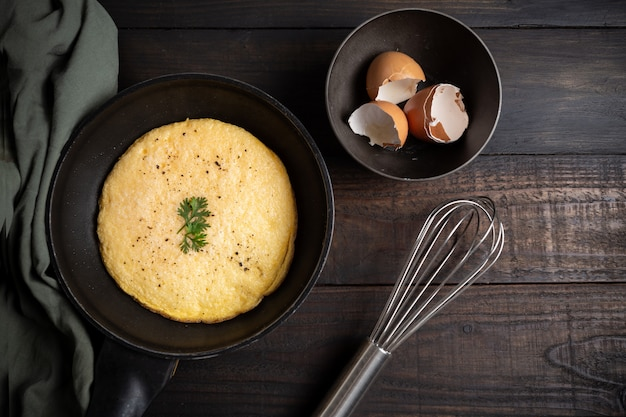 Omelett in einer pfanne auf holz.
