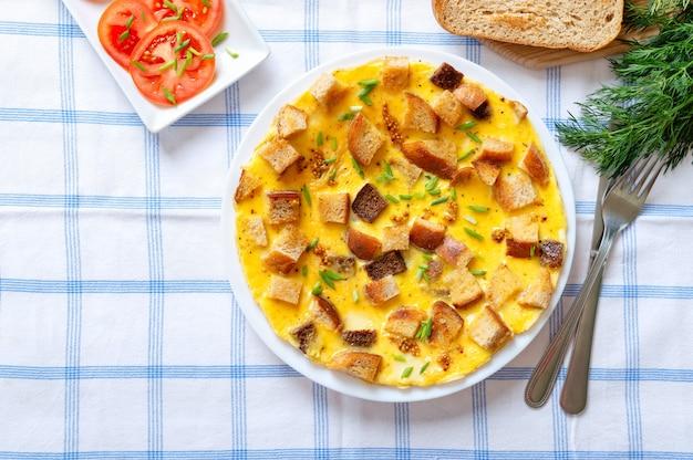 Omelett mit brot- und käsestücken in einem teller mit besteck auf einer karierten tischdecke