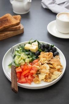Omelett mit frischem gemüse: rucola, tomaten, gurken, oliven, käse. dunkler tisch. draufsicht.