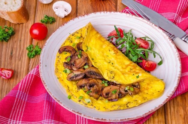 Omelett mit gebratenen pilzen und kräutern. rustikaler stil.