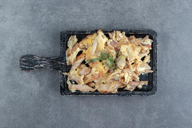 Omelett mit geschnittenem fleisch auf schwarzem brett.