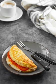 Omelett mit käse und tomaten und einer tasse kaffee. gesundes hausgemachtes omelett zum frühstück.