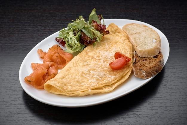 Omelett mit lachs, kräutern und ciabatta-toast auf einer dunklen oberfläche