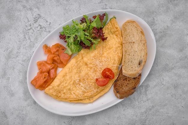 Omelett mit lachs, kräutern und ciabatta-toast auf einer hellen oberfläche