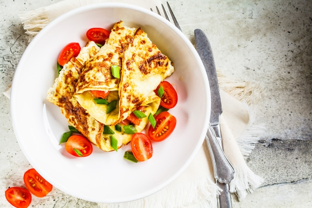 Omelett mit lachsen, käse und frühlingszwiebeln auf weißer platte, draufsicht