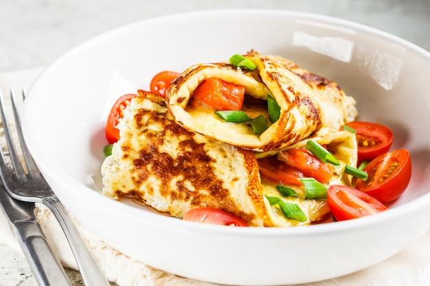 Omelett mit lachsen, käse und frühlingszwiebeln auf weißer platte