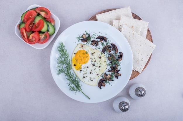 Omelett mit pfeffer und teller mit tomaten und gurken.