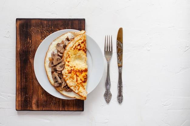 Omelett mit pilzen auf einem holzbrett