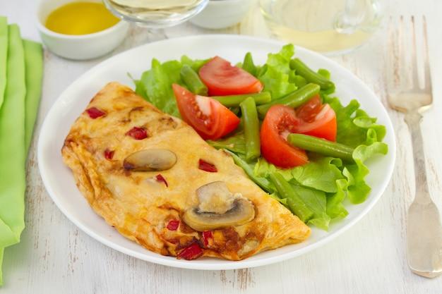 Omelett mit pilzen und pfeffer auf der platte