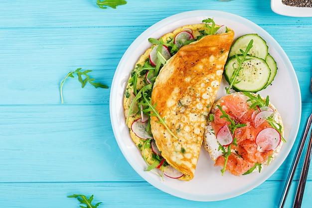 Omelett mit radieschen, grünem rucola und sandwich mit lachs auf weißem teller