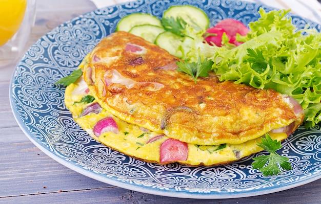 Omelett mit radieschen, roten zwiebeln und frischem salat