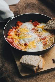Omelett mit rotem pfeffer in einer pfanne in der nähe von geschnittenem schwarzbrot auf einem holzbrett