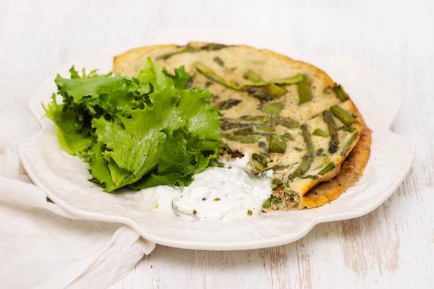 Omelett mit spargel, frischem salat und sauce auf weißem teller