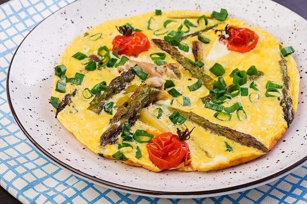 Omelett mit spargel und tomate zum frühstück auf einem holztisch.