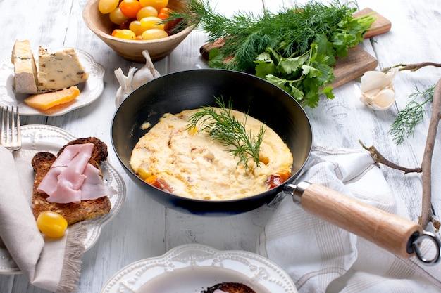 Omelett mit tomate in einer pfanne zum frühstück, käse und grüns auf einem weißen hölzernen hintergrund