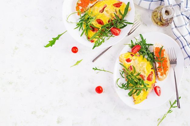 Omelett mit tomaten, käse, schinken und sandwich mit rotem kavier auf teller. frittata - italienisches omelett. draufsicht, overhead, speicherplatz