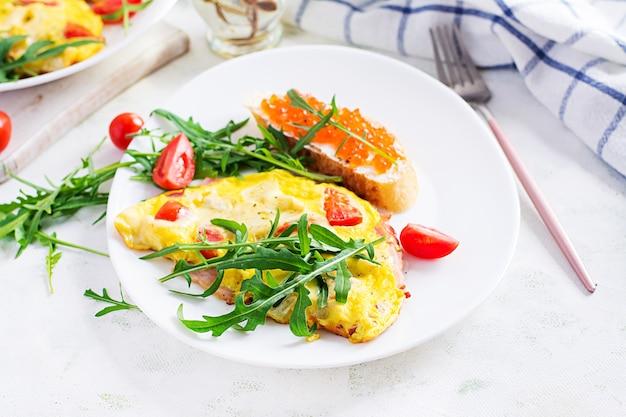 Omelett mit tomaten, käse, schinken und sandwich mit rotem kavier auf teller. frittata - italienisches omelett.