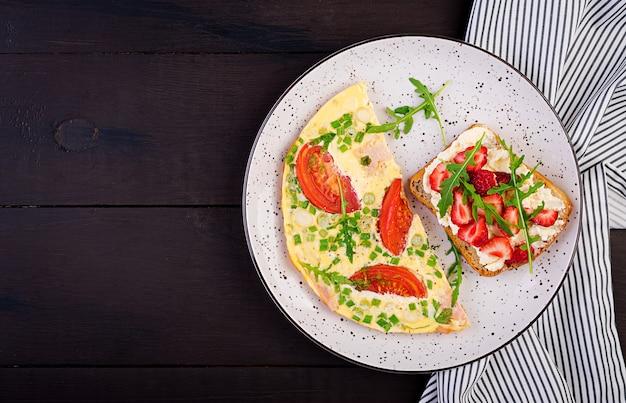 Omelett mit tomaten, schinken, frühlingszwiebel und sandwich mit erdbeere auf dunkler tabelle, draufsicht