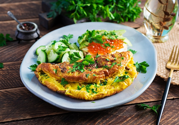 Omelett mit waldpilz, fusilli-nudeln und sandwich mit rotem kaviar, avocado auf teller. frittata - italienisches omelett.