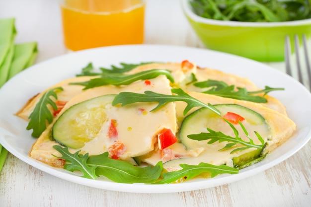 Omelett mit zucchini auf der platte und orangensaft