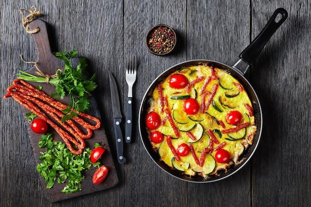 Omelett mit zucchini, dünnen geräucherten würsten und tomaten in einer bratpfanne auf einem dunklen holztisch mit zutaten auf einem schneidebrett, horizontale ansicht von oben, flach