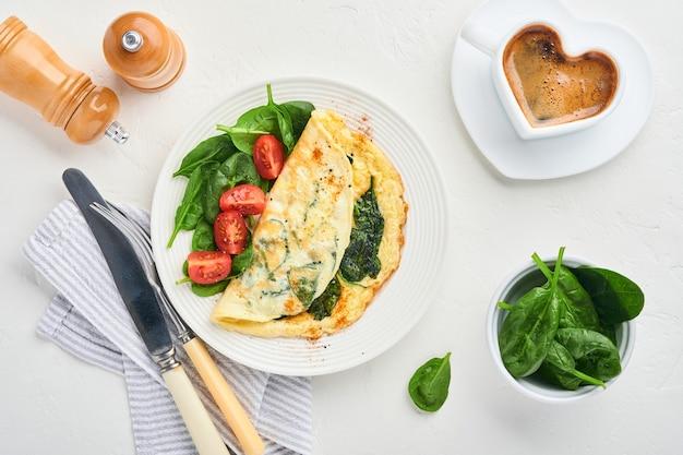 Omelett oder omelette mit spinat, kirschtomate und pfeffergewürz auf einem weißen teller, auf weißem hintergrund. ansicht von oben.
