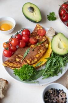 Omelett serviert mit avocado-kirschtomaten und rucola auf keramikplatte