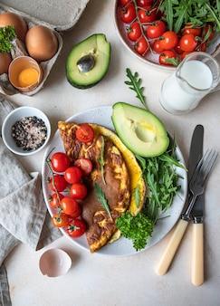 Omelett serviert mit avocado-kirschtomaten und rucola gesundes und leckeres keto-frühstück oder brunch