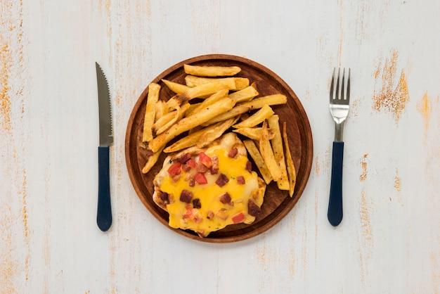 Omelett und pommes-frites auf hölzernem brett auf schmutz malten schreibtisch