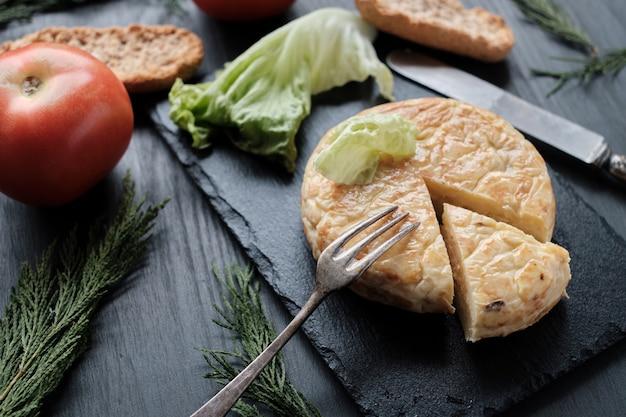 Omelett von kartoffeln auf schiefer und schwarzem hintergrund