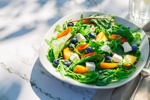 Omemade-salat mit nektarinen, blaubeeren, rucola und feta-käse auf weißem marmorhintergrund