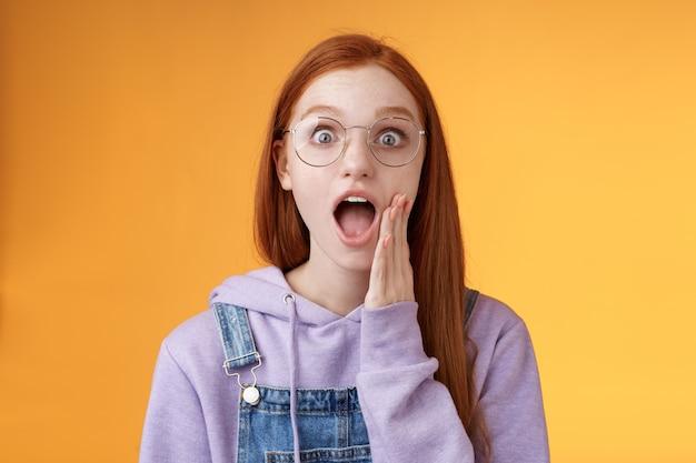 Omg auf keinen fall. attraktive schockiert gewundert rothaarige amüsierte hipster-frau moderner teenager fallen kiefer keuchend große augen überrascht stehend erstaunt reagieren schockiert schockiert kamera berühren wange aufgeregt